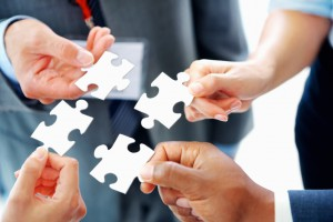 Portrait of business people solving puzzle together at office